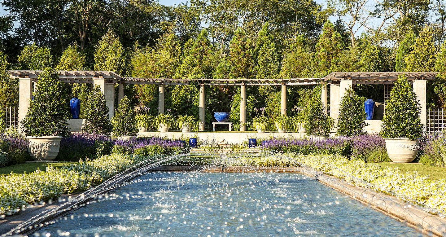 An outdoor garden portico with reflecting pool and fountains