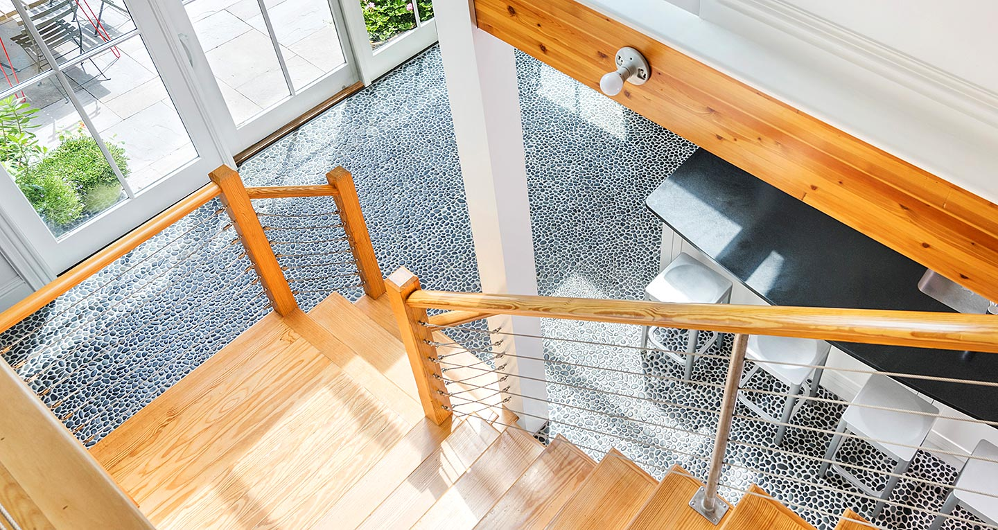 A brightly sunlight light wood staircase looking down into kitchen
